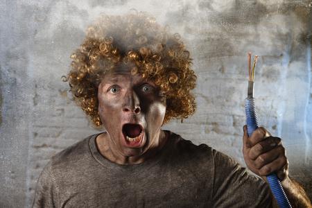 Jeune homme avec perruque frisée drôle tenant fumer câble électrique après accident domestique avec le visage brûlé sale et choc électrocutée expression dans l'électricité concept de réparations de bricolage de danger en noir fumée fond Banque d'images - 53337686