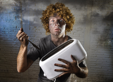 electric shock: young man electrocuted trying to get toast out of toaster with knife suffering domestic accident with dirty burnt face in funny shock expression screaming crazy in electricity danger concept Stock Photo