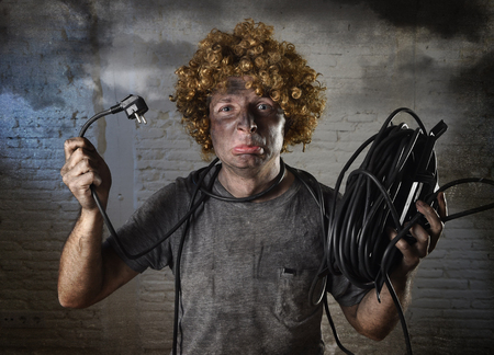 electrocute: young man with funny curly wig holding electrical cable smoking after domestic accident with dirty burnt face and shock electrocuted expression in electricity DIY repairs danger concept in black smoke background