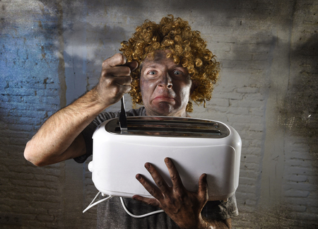 burnt out: young man electrocuted trying to get toast out of toaster with knife suffering domestic accident with dirty burnt face in funny shock expression screaming crazy in electricity danger concept Stock Photo