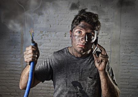 młody człowiek gospodarstwa kabla elektrycznego palenie po awarii elektrycznej ze spalonego brudnej twarzy w rozpaczliwej śmieszne wypowiedzi dzwoniącej z telefonu komórkowego z prośbą o pomoc w energię elektryczną naprawy DIY koncepcja zagrożenia Zdjęcie Seryjne