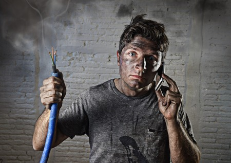 electric shock: young man holding electrical cable smoking after electrical accident with dirty burnt face in funny desperate expression calling with mobile phone asking for help in electricity DIY repairs danger concept
