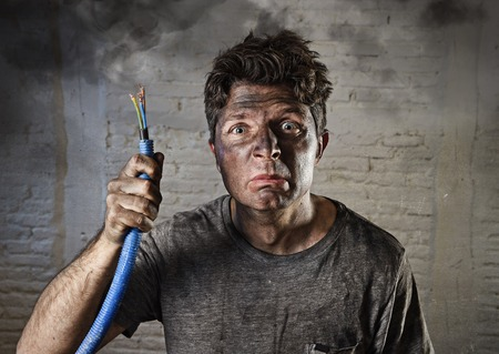 electrocute: young man holding electrical cable smoking after domestic accident with dirty burnt face in funny sad expression in electricity DIY repairs danger concept  in black smoke background