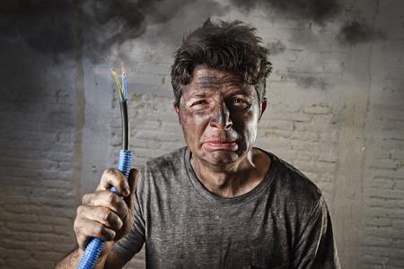 jonge man met elektrische kabel met roken na huiselijk ongeval met vuile verbrand gezicht in grappige droevige uitdrukking in elektriciteit DIY reparaties gevaar concept in zwarte rook achtergrond Stockfoto