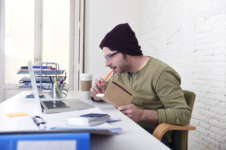 self employed: young attractive hipster businessman with take away coffee working from his home office as freelancer wearing beanie looking busy in self employed business model success Stock Photo