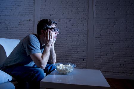geek: hombre joven adicto a la televisi�n sentado en el sof� de casa viendo televisi�n y comiendo palomitas de ma�z que llevaba divertidas gafas nerd y friki mirando hipnotizado comedia pel�cula de disfrutar o deportes en directo por la noche Foto de archivo