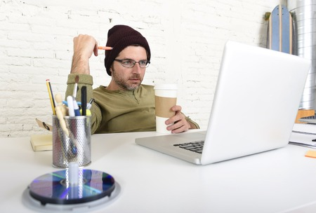 self employed: young attractive hipster businessman holding take away coffee working from his home office as freelancer wearing beanie looking busy in self employed business model success