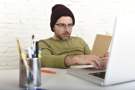 self employed: young attractive hipster businessman working from his home office as freelancer wearing casual beanie and glasses looking busy in self employed business model success