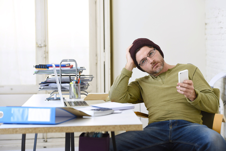 self employed: young attractive hipster businessman working from home office as freelancer wearing casual beanie looking thoughtful using mobile phone in self employed business model success Stock Photo