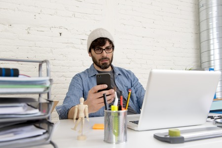 30s: corporate portrait of young hispanic attractive hipster businessman on his 30s working at modern home office with computer laptop using mobile phone in creative freelancer concept Stock Photo