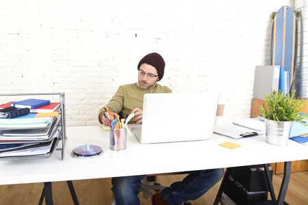 self employed: young attractive hipster businessman working from his home office as freelancer wearing casual jeans beanie and glasses looking busy in self employed business model success