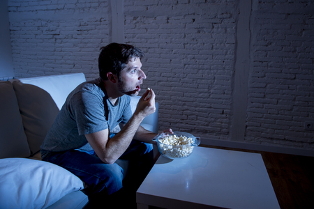 mesmerized: young television addict man sitting on home sofa watching TV and eating popcorn looking mesmerized enjoying movie sitcom or live sport at night