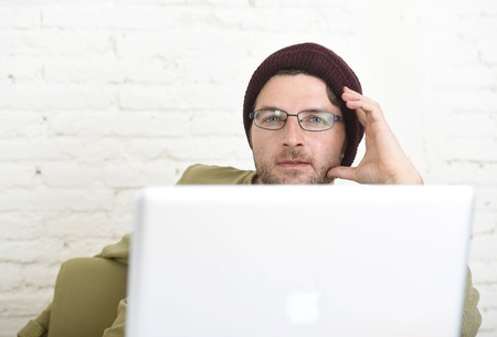 self employed: young attractive hipster businessman working from his home office as freelancer wearing casual beanie and glasses looking happy and confident in self employed business model success