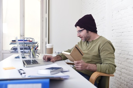 self employed: young happy hipster businessman working from his home office as freelancer wearing casual beanie and glasses looking busy in self employed business model success