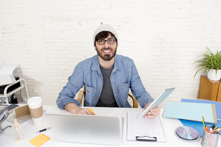 businessman working at his computer: corporate portrait of young hispanic attractive hipster businessman on his 30s working at modern home office with computer laptop using digital tablet pad in creative freelancer concept Stock Photo