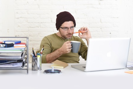beanie: young hipster businessman working from his home office as freelancer wearing casual beanie and glasses looking busy in self employed business model success Stock Photo