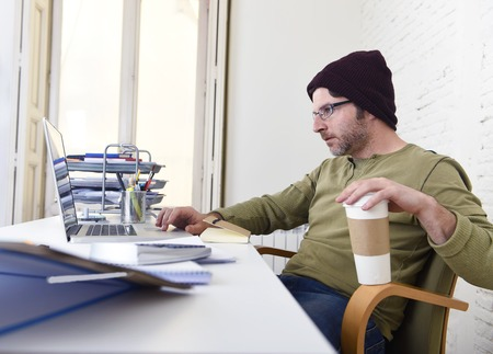 self employed: young hipster businessman working from his home office as freelancer wearing casual jeans and beanie holding take away coffee looking busy in self employed business model success