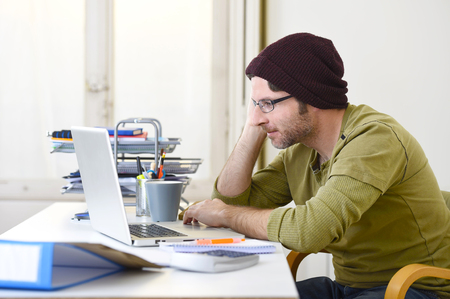 self employed: corporate portrait of young happy hipster businessman working with computer laptop at home office as freelancer in modern creative designer worker and self employed business model concept