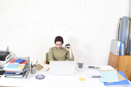 self employed: corporate portrait of young thoughtful hipster businessman working with computer laptop at home office as freelancer in modern creative designer worker and self employed business model concept