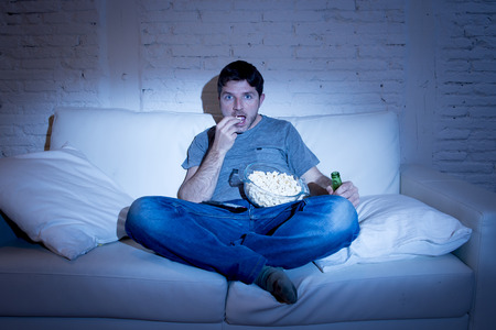mesmerized: young television addict man sitting on home sofa watching TV eating popcorn and drinking beer bottle looking mesmerized enjoying movie sitcom or live sport at night Stock Photo
