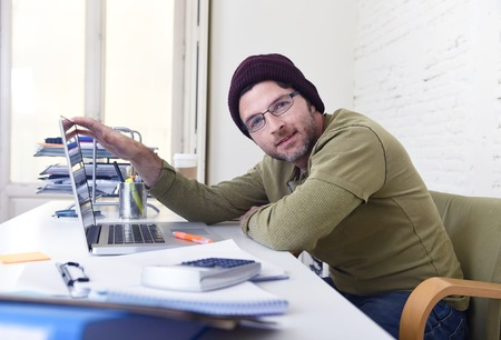 self employed: young happy hipster businessman working from his home office as freelancer wearing casual beanie jeans and glasses smiling in self employed business model success