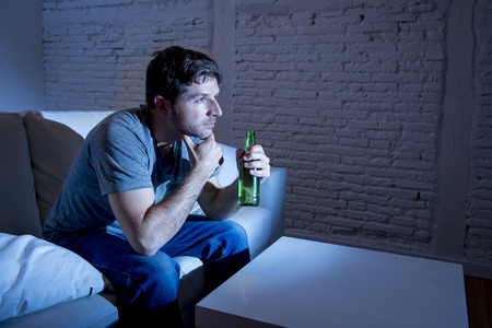 mesmerized: young television addict man sitting on home sofa watching TV and drinking beer bottle looking mesmerized enjoying movie sitcom or live sport at night Stock Photo
