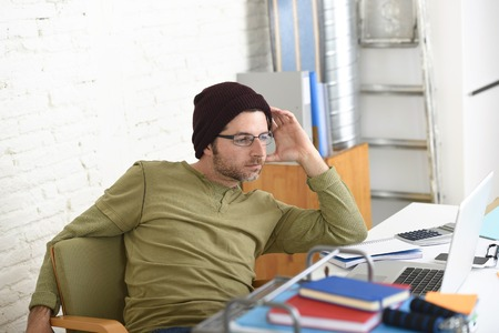 self employed: young attractive hipster businessman working from his home office as freelancer wearing beanie and glasses looking relaxed and successful in self employed business model success