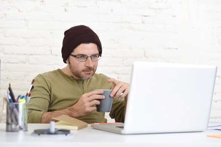 self employed: young hipster businessman working from his home office as freelancer wearing casual beanie and glasses looking busy in self employed business model success Stock Photo