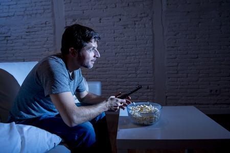 joven hombre feliz adicto a la televisión sentado en el sofá de casa viendo la televisión comiendo palomitas de maíz usando el control remoto disfrutando de comedia película o deportes en directo por la noche Foto de archivo