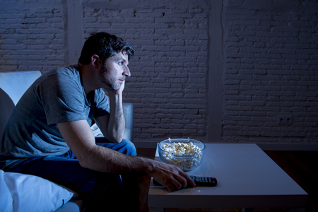 bowls of popcorn: young television addict man sitting on home sofa watching TV eating popcorn using remote control looking bored and tired zapping foe another movie sitcom or live sport at night