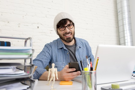 businessman working at his computer: corporate portrait of young hispanic attractive hipster businessman on his 30s working at modern home office with computer laptop using mobile phone in creative freelancer concept Stock Photo