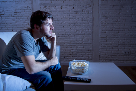 mesmerized: young happy television addict man sitting on home sofa watching TV and eating popcorn looking mesmerized smiling while enjoying movie sitcom or live sport at night