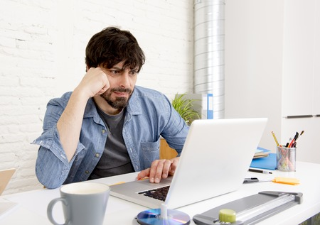 self employed: corporate portrait of young hispanic attractive hipster businessman on his 30s working at modern home office with computer laptop in creative freelancer and self employed business model