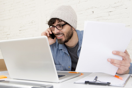 businessman working at his computer: young Hispanic attractive hipster businessman on his 30s working at modern home office with computer laptop talking on mobile phone smiling  happy  in freelance business concept Stock Photo