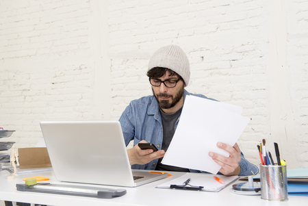 businessman working at his computer: corporate portrait of young Hispanic attractive hipster businessman on his 30s working at modern home office with computer laptop using mobile phone in freelance creative business concept