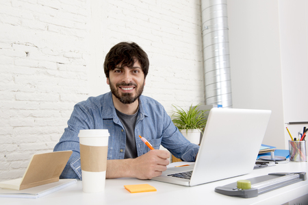 businessman working at his computer: corporate portrait of young hispanic attractive hipster businessman on his 30s working at modern home office with computer laptop in creative freelancer and self employed business model