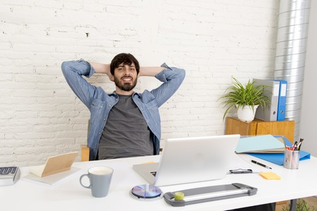 businessman working at his computer: corporate portrait of young hispanic attractive hipster businessman on his 30s working at modern home office with computer laptop looking happy and satisfied in creative freelancer success Stock Photo