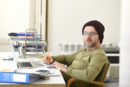 beanie: corporate young attractive hipster businessman working with computer laptop at home office as freelancer in casual beanie desk smiling happy and confident  in creative freestyle business
