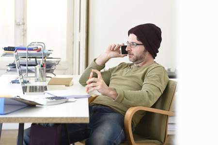 beanie: corporate portrait of young happy hipster businessman working from modern  home office as freelancer wearing casual beanie talking on mobile phone in creative freestyle business people