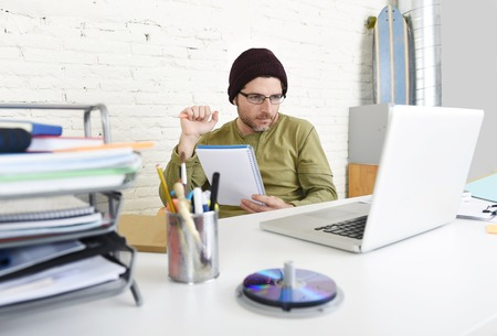 self employed: corporate portrait of young busy hipster businessman working with computer laptop at home office as freelancer in modern creative designer worker and self employed business model concept