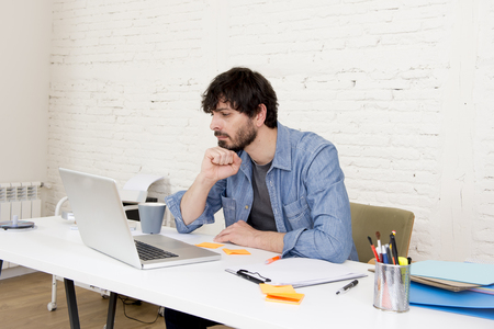 busy beard: corporate portrait of young hispanic attractive hipster businessman working busy at modern home office with computer laptop dressing casual denim in creative freelancer business concept