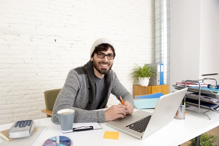 30s: young hispanic attractive and happy hipster 30s businessman working at modern home office with computer laptop dressing casual in creative freelancer business success concept