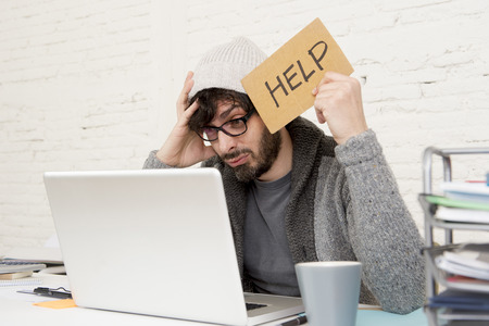 30s: busy hispanic hipster 30s businessman working tired at home office with computer laptop dressing casual asking for help looking overworked  suffering stress and depression Stock Photo