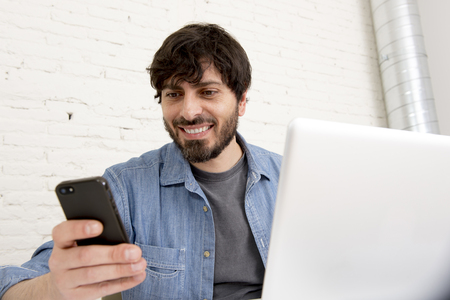 businessman working at his computer: corporate portrait young Hispanic attractive hipster businessman on his 30s working at modern home office with computer laptop using mobile phone wearing casual denim shirt and beard Stock Photo