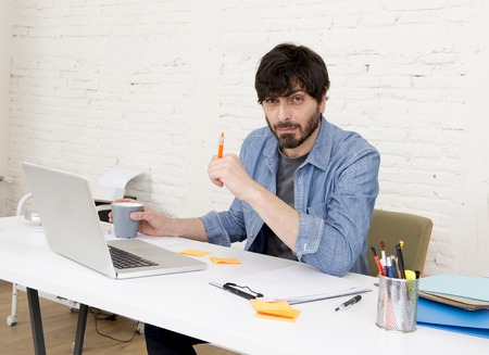 casua: young hispanic attractive  hipster 30s businessman working busy at modern home office with computer laptop dressing casua denim in creative freelancer business success concept