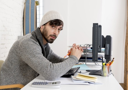 beanie: young worried businessman in cool hipster beanie look looking desperate having problem working in stress at home office with computer in business frustration overworked and deadline project Stock Photo