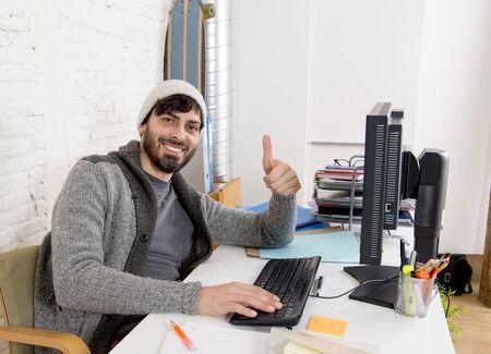trabajando en computadora: hombre joven y atractiva en gorrita inconformista y hombre de negocios de moda del estilo de trabajo feliz en la oficina en casa con ordenador de escritorio como diseñador creativo en busca confianza satisfecho y éxito Foto de archivo