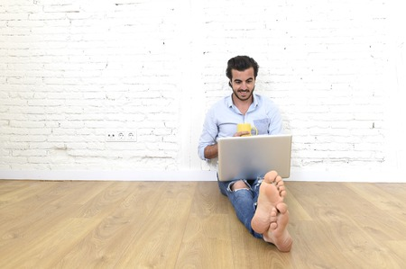 young attractive Latin man in hipster and modern casual style look sitting on unfurnished living room home floor working on laptop computer smiling happy in internet communication concept
