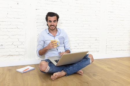 unfurnished: young attractive latin man in hipster and modern casual style look sitting on unfurnished living room home floor working on laptop computer drinking coffee in internet communication concept