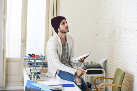 busy beard: young trendy businessman in cool hipster beanie and informal look writing on pad working thoughtful at modern home office as creative designer in freelance business success concept